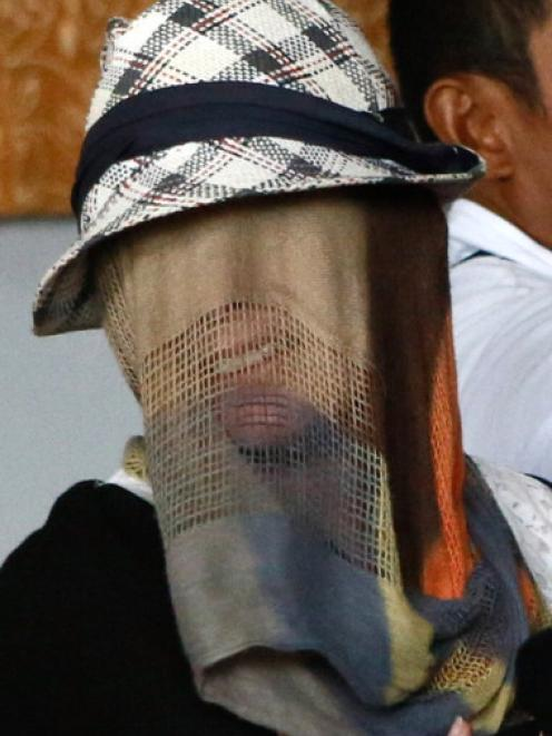 Schapelle Corby, with her face covered, reports for a parole hearing before being released on...