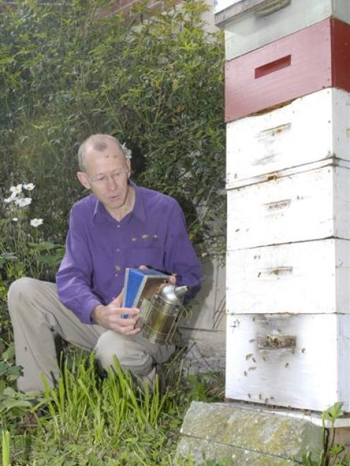 School teacher, reviewer and now author Raymond Huber smokes his backyard beehive. Photo by...