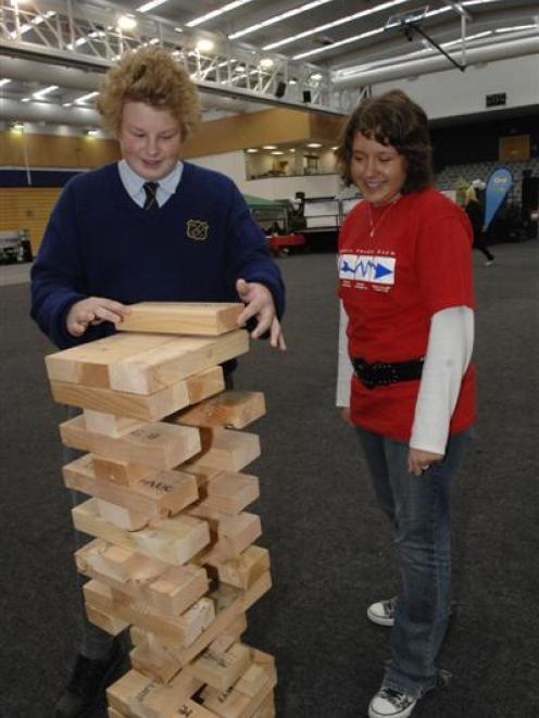 """Tokomairiro High School pupil Tony Powick (15) moves a supersize """"Jenga"""" block, watched by Queens..."""