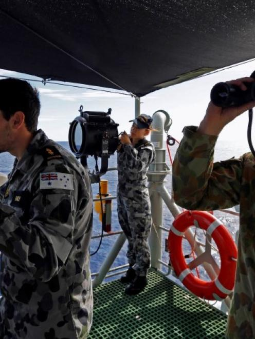 Seamen aboard the Australian Navy ship HMAS Perth look towards the HMAS Success during manoeuvres...
