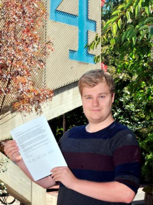Second-year law student and class representative Daniel Doughty  holds a petition calling for...
