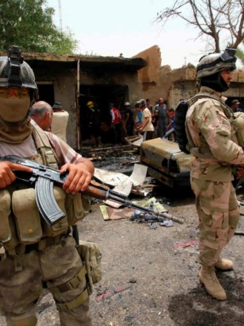 Security forces stand guard at the site of a recent car bomb attack at a market in the town of...