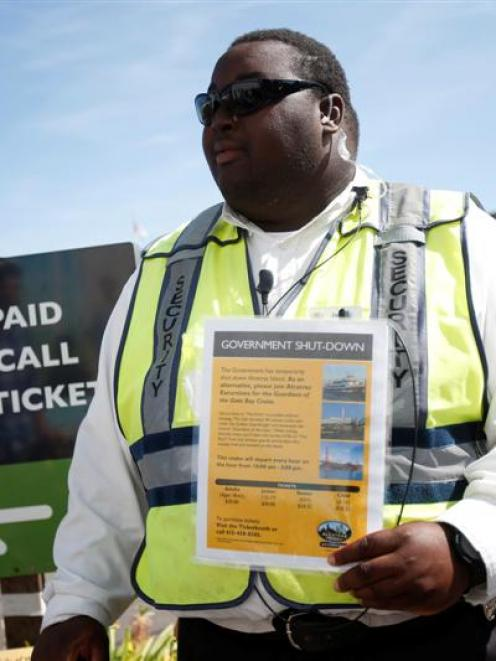 Security officer Jarvis Landlum holds a sign informing people on the government shutdown of...