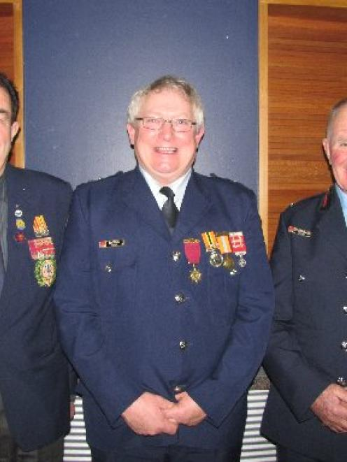 Senior station officer Ken Tisdall (centre) was Saturday evening honoured with the gold star...