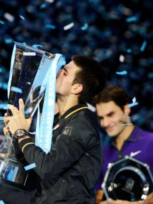 Serbia's Novak Djokovic kisses the trophy after beating Switzerland's Roger Federer in their...