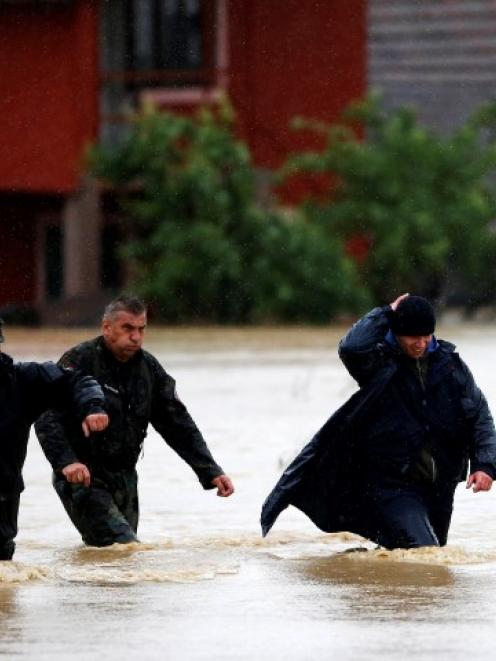 Serbian gendarmerie police officers walk in a flooded street in the town of Lazarevac, south of...