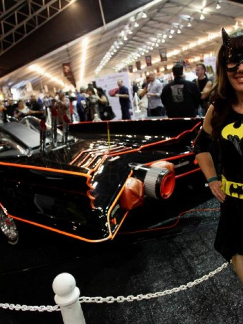 Shelli Mart, dressed in a costume, poses next to the original Batmobile during the Barrett...