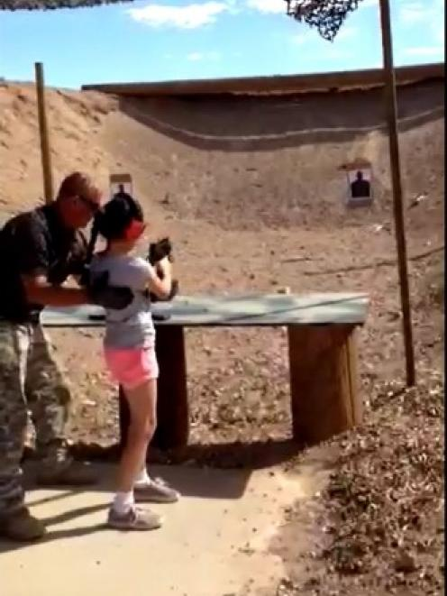 Shooting instructor Charles Vacca stands next to a 9-year-old girl at the Last Stop shooting...