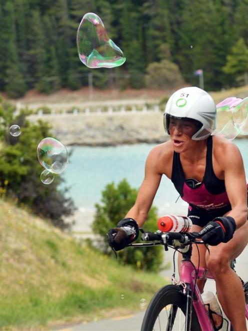 Simone Maier rides through bubbles released by supporters as she climbs the hill into Hawea...