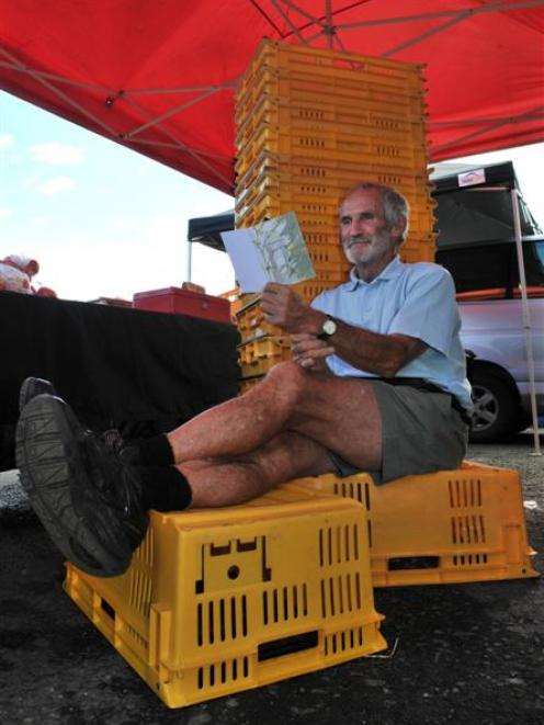 Sitting in front of crates that had been full of strawberries and cherries, Otago Farmers Market...