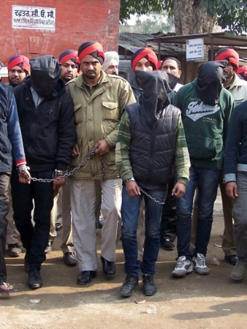 Six men (faces covered) accused of a gang rape in Punjab are escorted by police to a court at...