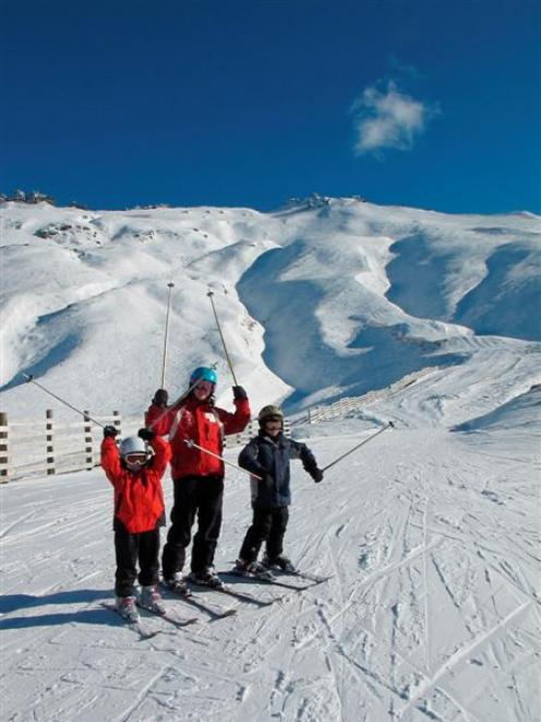Skiers celebrate winter at Treble Cone yesterday after a run down the Saddle Basin.