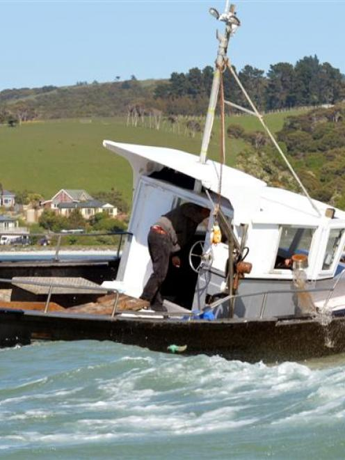Skipper Colin Webb tosses a pot of water out the wheelhouse window in an attempt to refloat the...