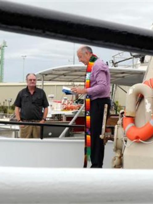 Skipper Martin Finnie (left) and deckhand John James watch Fr Mark Chamberlain bless Sirocco at...