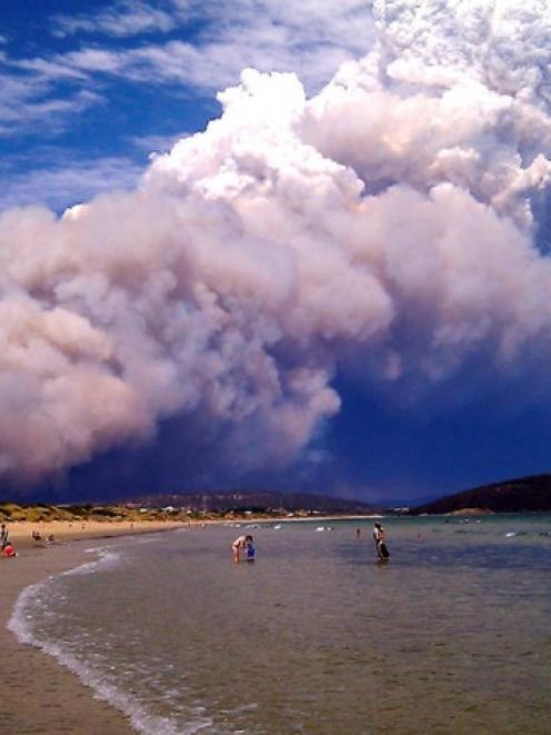Smoke from a bushfire billows over a beach at Carlton, about 20km east of Hobart last week. New...