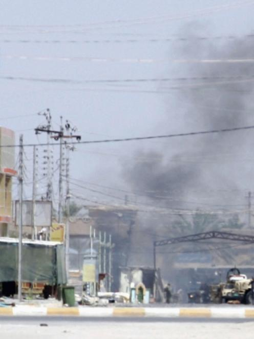 Smoke rises after clashes between Iraqi security forces and followers of Iraq's Shi'ite cleric...