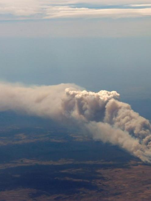 Smoke rises from the Yarrabin bushfire, burning out of control near Cooma, about 100km south of...