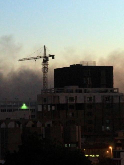 Smoke rises out of central Khartoum as cars burn during a demonstration over the deaths of four...