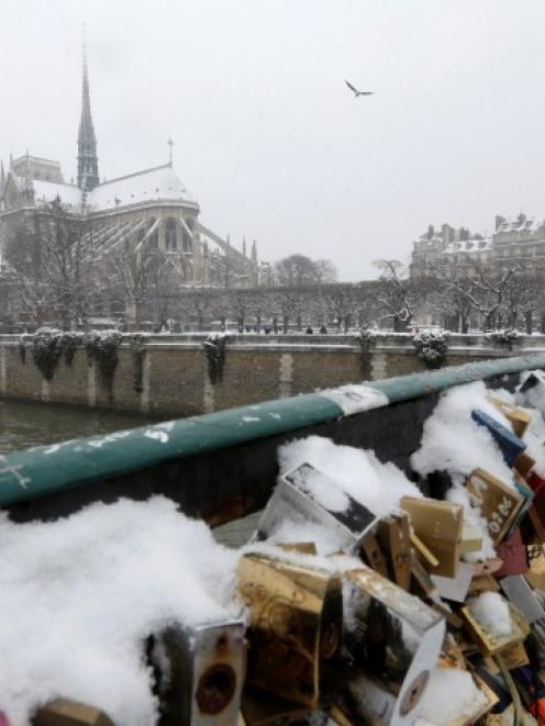 Snow covers some of thousands of padlocks clipped by lovers on to the railings of Pont de l...