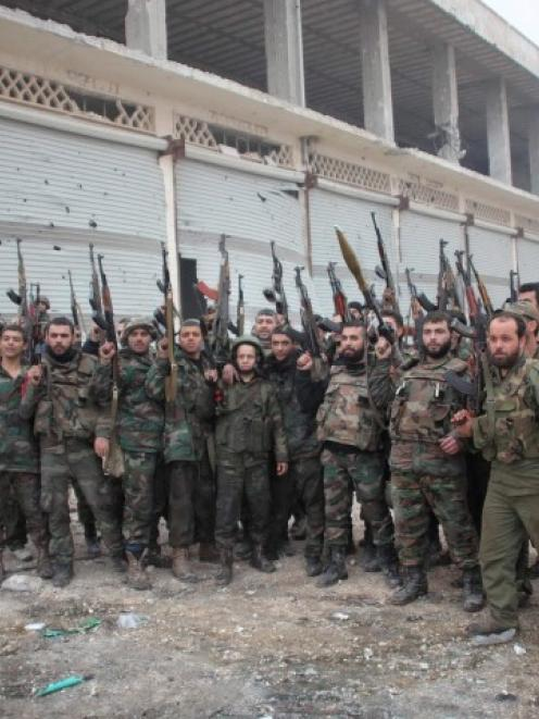 Soldiers loyal to Syria's President Bashar al-Assad pose for a photograph in the Aleppo town of...