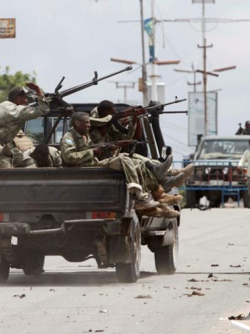 Somali government soldiers ride to take up position outside the Parliament building during a...
