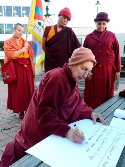 Sonam Chokyi writes a translation of a message of protest from Geshe Jampa Tenzin (back, centre)...