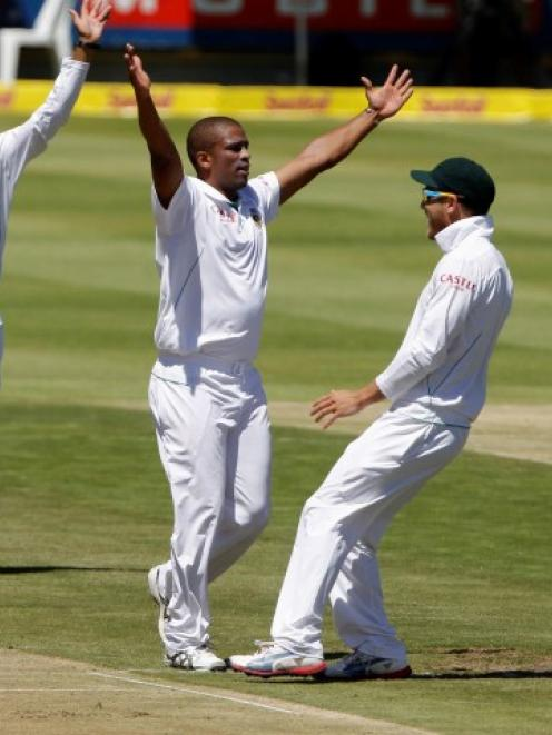 South Africa's Vernon Philander (2nd L) celebrates with teammates after taking the wicket of New...