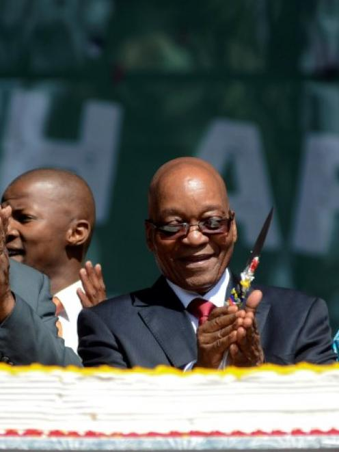 South African President Jacob Zuma (C) cuts a cake as crowds gather to celebrate Freedom Day at...