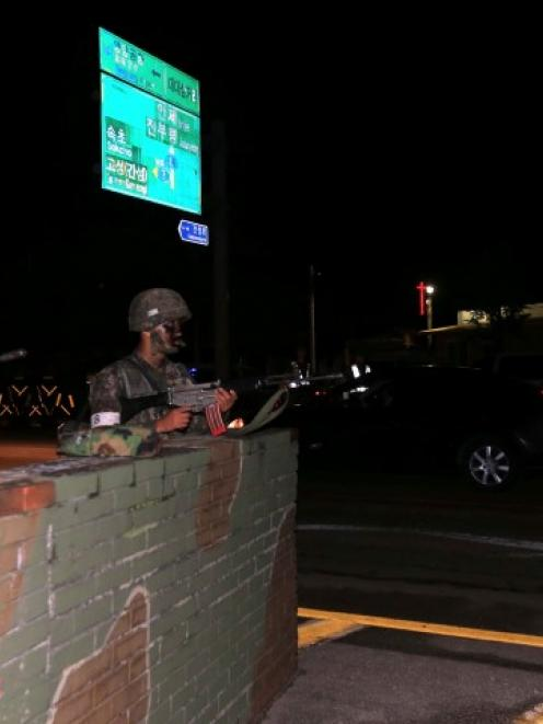 South Korean soldiers stand guard at a temporary checkpoint during a search for the soldier who...