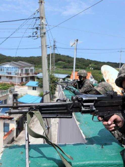 South Korean soldiers take their positions as part of the search for the conscript soldier who...