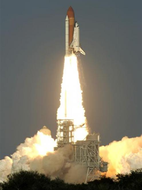 Space shuttle Discovery lifts off from the Kennedy Space Centre in Cape Canaveral, Florida on its...