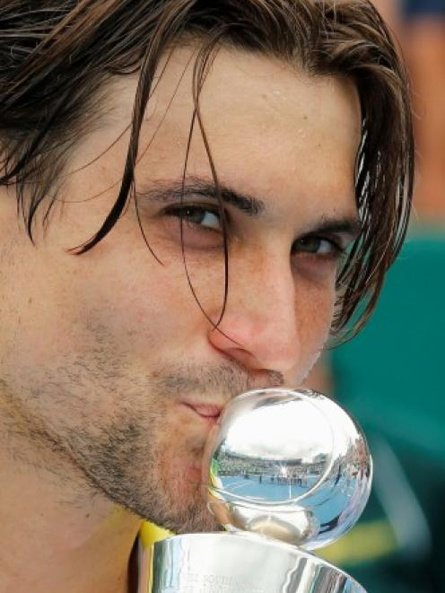 Spain's David Ferrer kisses the trophy after beating Germany's Philipp Kohlschreiber to win the...