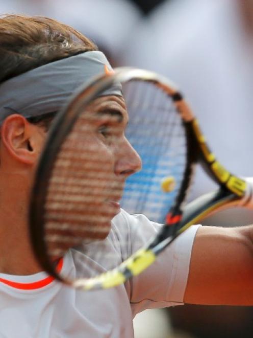 Spain's Rafael Nadal hits a return to Stanislas Wawrinka of Switzerland during their men's...