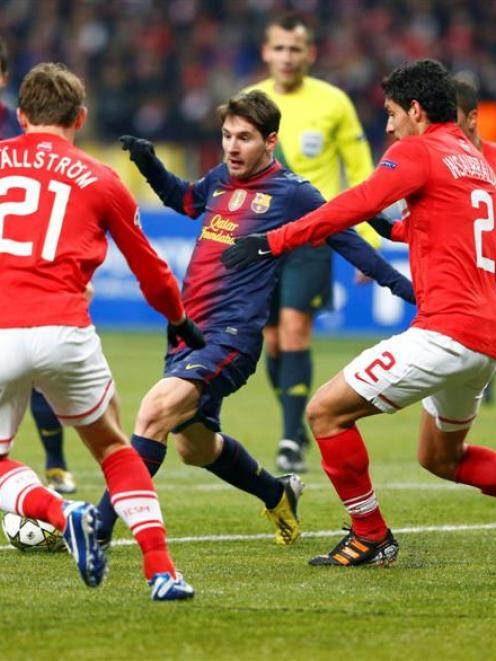 Spartak Moscow's Kim Kallstrom and Juan Insaurralde  fight for the ball with Barcelona's Lionel...
