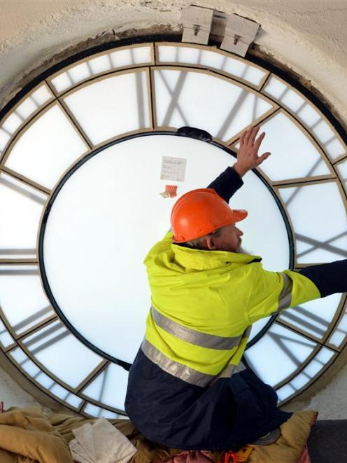Specialist glazier Peter Mackenzie works on the Iona Church clock face in Port Chalmers. Photo by...