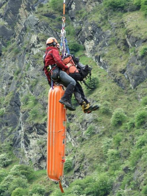 Specialist rescuers are lifted by helicopter on to a Queenstown cliff face as part of a training...