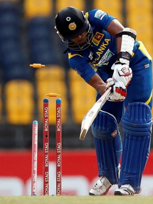 Sri Lanka's Dinesh Chandimal is bowled out by New Zealand's Tim Southee during their final One...