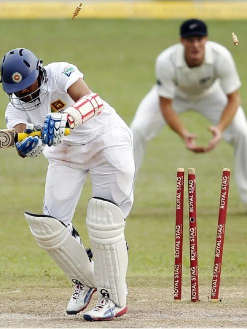 Sri Lanka's Tillakaratne Dilshan (L) is bowled out by New Zealand's Tim Southee during the second...