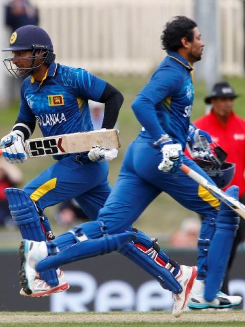 Sri Lankan batsmen Tillakaratne Dilshan (R) and Kumar Sangakkara cross while running during their...