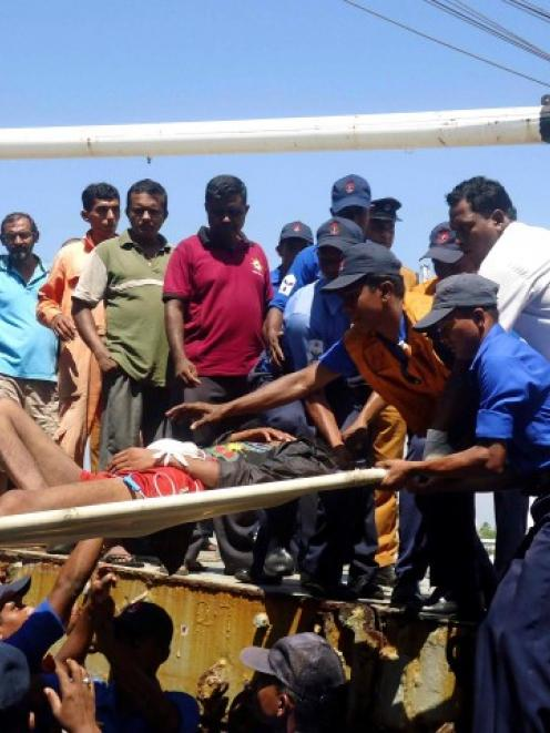 Sri Lankan navy soldiers carry an injured man as part of a rescue of 32 Myanmar nationals who...