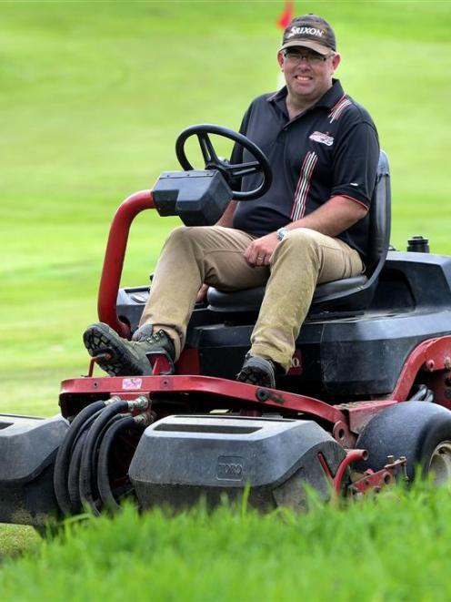 St Clair green keeper Andrew Hobbs relaxes on his mower in front of the new 18th green yesterday....
