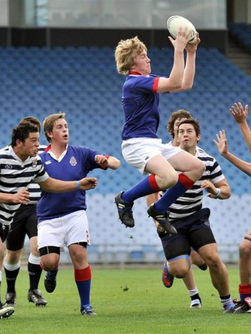 St Kevin's College flanker Rory McNamara is under pressure as he safely takes in the high ball...