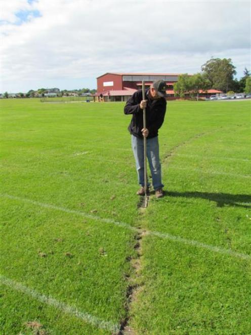 St Kevin's College head groundskeeper Allan Grant repairs a damaged school sports field. Photo by...
