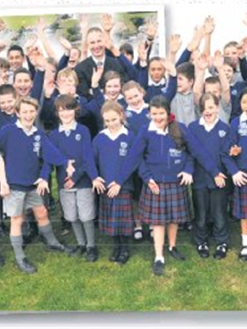 St Mary's School principal Mike Brosnahan and pupils celebrate on the Mosgiel site where their...