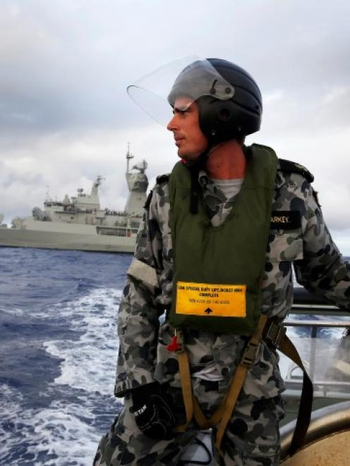 Standing in a rigid hull inflatable boat launched from the Australian Navy ship HMAS Perth,...