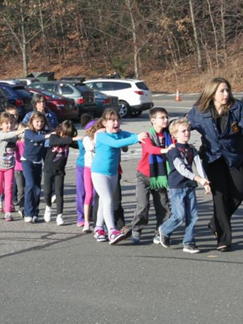 State police personnel lead children from the Sandy Hook Elementary School. REUTERS/Newtown Bee...