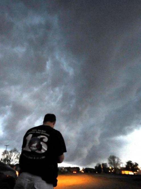 Storm chaser Brad Mack takes photos as low-level thunder storm supercells pass over Bearden,...
