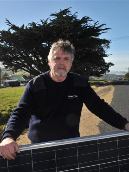 Stu Nicholson holds a solar panel set  to be installed on the roof of his Brighton home, which is...