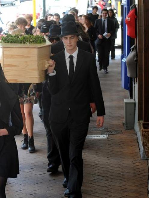 Students and environmentalists carry a coffin through Dunedin to raise awareness of environmental...