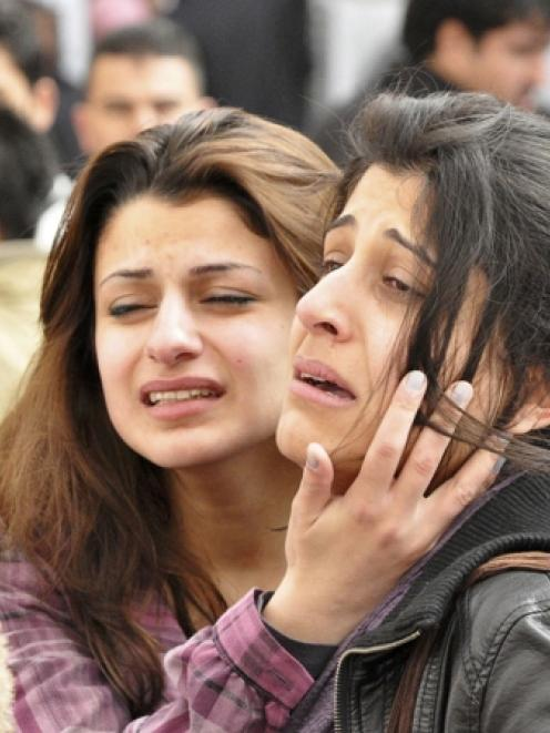 Students grieve after a fellow student shot dead his American teacher at a school in Sulaimaniya,...